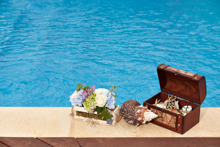 Concept background summer pool image shot of a trunk filled with shells and a ship, snail and flowers, copy space photo