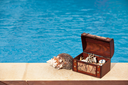 Concept background summer pool image shot of a trunk filled with shells and a ship, snail, copy space photo