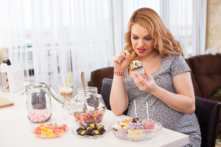 courtain: Pregnant young woman having a cupcake, sitting at the kitchen table full of sweets