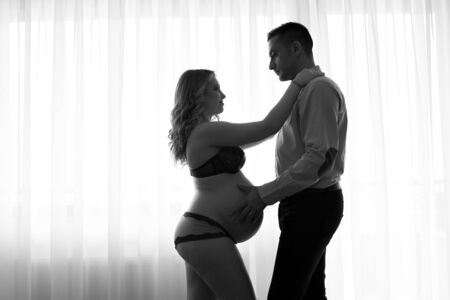 Black and white artistic contre-jour picture of a pregnant woman and her husband holding his hands on her belly photo