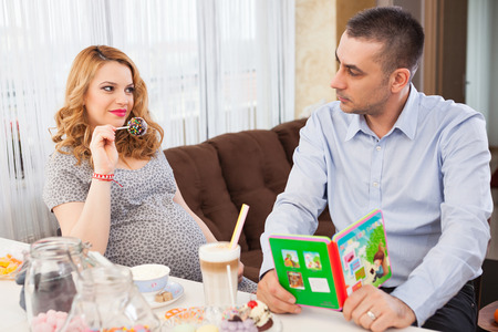 Picture of a pregnant woman showing a lollipop to her husband, sitting at the kitchen table photo