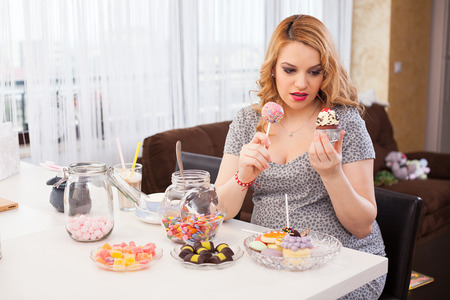 craving: Young pregnant woman trying to decide what cookie to eat, sitting at the kitchen table full of sweets