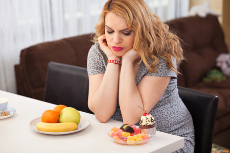 Pregnant young woman trying to decide whether to eat fruits or sweets, sitting at the kitchen table photo