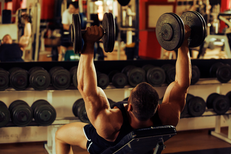 artistic shot, golden retouch, of a young bodybuilder hard training in the gym: incline dumbbell press