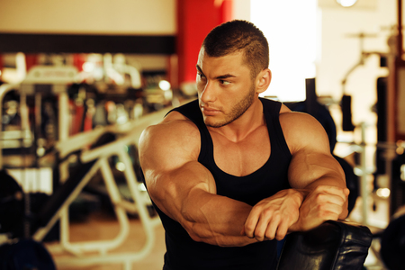 retouch: artistic shot, golden retouch, of a young bodybuilder hard training in the gym: taking a break