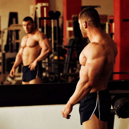 artistic shot, golden retouch, of a young bodybuilder posing in the mirror at the gym: Stock Photo