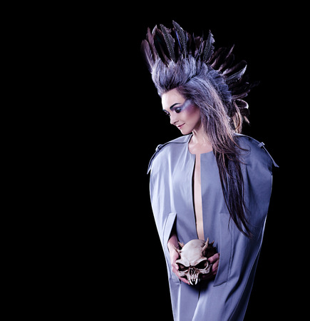 dark fashion shot of a woman holding a evil skull, crazy hairstyle with feathers Reklamní fotografie