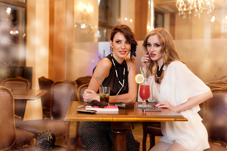 two fashion women in a bar, gossip