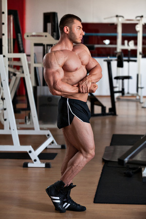 young professional bodybuilder posing in the gym: side chest