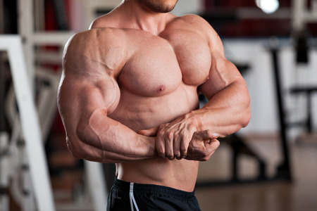 huge: detail of a bodybuilder posing in the gym: side chest Stock Photo