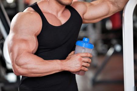 hombres musculosos: joven culturista profesional en el gimnasio, bebiendo un batido de prote�nas Foto de archivo