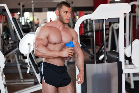 lean out: young professional bodybuilder in the gym, drinking a protein shake Stock Photo