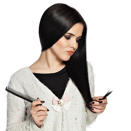 split ends: Sad brunette young woman holding her hair, and a comb.  Gorgeous white caucasian female model feeling disappointed about the split ends. Stock Photo