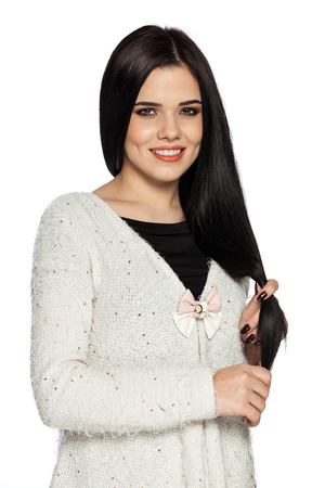 Smiling brunette young woman holding her hair.  Gorgeous white caucasian female model feeling happy about her healthy hair.