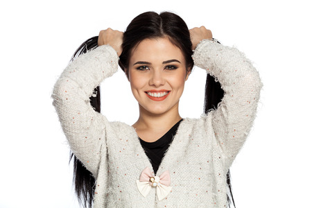 Smiling brunette young woman holding two ponytails.  Gorgeous white caucasian female model feeling happy about her healthy hair.