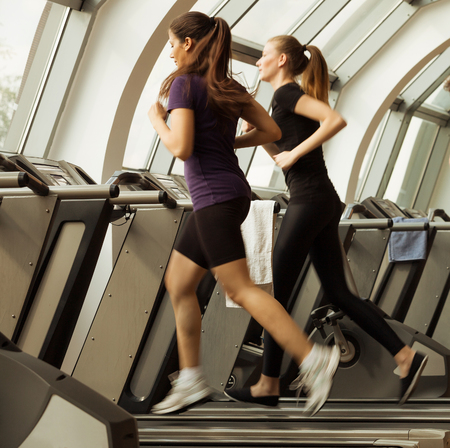 treadmill: gym shot - two young women running on machines, treadmill
