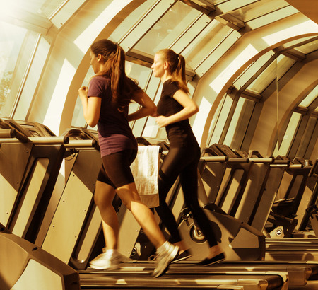 gym shot - two young women running on machines, treadmill, golden look Reklamní fotografie