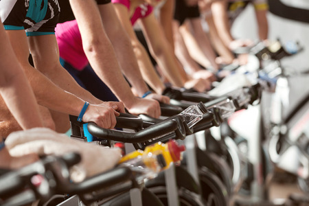 indoors: gym detail shot - people cycling; spinning class Stock Photo