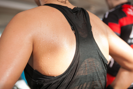 detail gym shot - sweat skin of a womans back; spinnig, aerobic class
