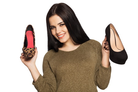 Smiling woman holding two shoes in her hands - shopping image. Gorgeous white caucasian female model isolated on white background. Reklamní fotografie
