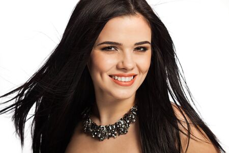 Gorgeous, smiling white caucasian female model isolated on white background, wearing a necklace. Reklamní fotografie
