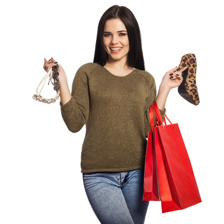 Smiling woman holding a shoe, a necklace, and red shopping bags. Gorgeous white caucasian brunette female model isolated on white background.