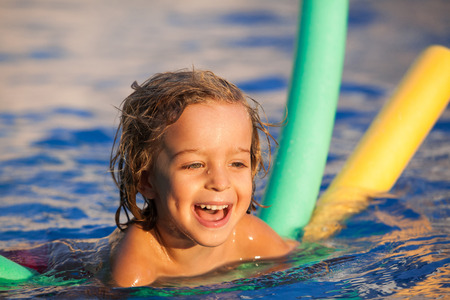 happy child in the pool, learning to swim with swimming noodle; warm sunset light