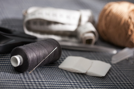 Different types of a tailors tools on a fabric: needle, scissors, measure, chalk, curl paper