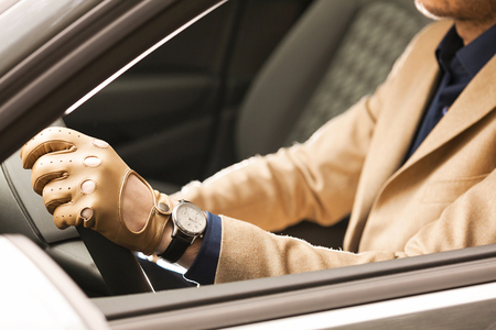 man driving, detail shot, hands on the steering wheel, wearing leather men gloves Reklamní fotografie