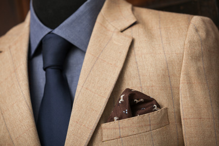 navy blue suit: detail shot of a business suit: blue shirt, navy tie and light brown coat