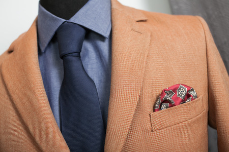 detail shot of a business suit: blue shirt, navy tie and light brown coat