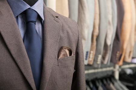 비즈니스 정장의 세부 샷 : 블루 셔츠, 네이비 넥타이와 갈색 코트; 백그라운드에서 정장을 많이