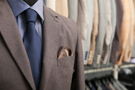 detail shot of a business suit: blue shirt, navy tie and brown coat; a lot of suits in the background Stok Fotoğraf