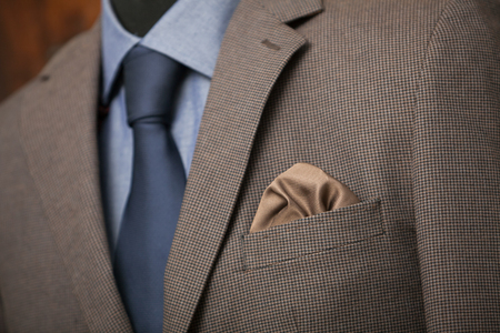 navy blue suit: detail shot of a business suit: blue shirt, navy tie and brown coat