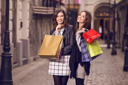 modelos posando: dos modelos de moda hermosas con bolsas de la compra, que presentan afuera; dos mujeres jóvenes riendo, divirtiéndose Foto de archivo