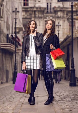 two beautiful fashion models posing outside with shopping bags; two young women walking in the city