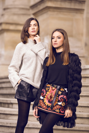 two beautiful fashion models posing outside wearing a grey sweater with leather shorts, studded chelsea ankle boots and a fringed cardigan, black T-shirt, embroidered A-line skirt  heeled ankle boots