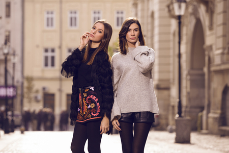 leather skirt: two beautiful fashion models posing outside wearing a grey sweater with leather shorts, studded chelsea ankle boots and a fringed cardigan, black T-shirt, embroidered A-line skirt  heeled ankle boots