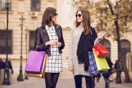 two beautiful fashion models posing outside with shopping bags; two young women laughing, having fun, wearing sunglasses Reklamní fotografie