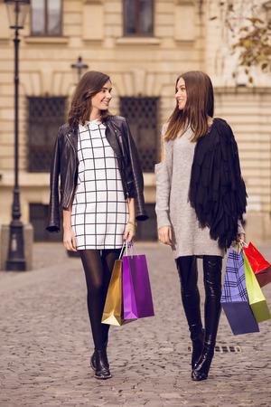 chicas de compras: dos modelos de moda hermosas que presentan afuera con bolsas de la compra; dos mujeres jóvenes riendo, divirtiéndose