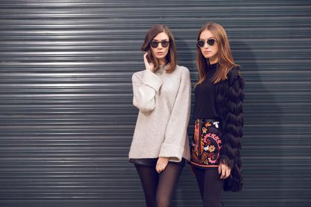 twee mooie mannequins poseren buiten het dragen van een grijze sweater met lederen broek, bezaaid chelsea enkellaarsjes en een omzoomd vest, zwart T-shirt, geborduurd A-lijn rok hakken enkellaars