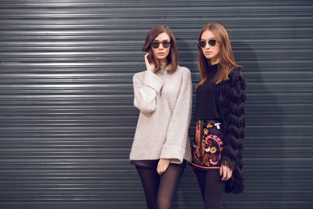 fashion: two beautiful fashion models posing outside wearing a grey sweater with leather shorts, studded chelsea ankle boots and a fringed cardigan, black T-shirt, embroidered A-line skirt  heeled ankle boots