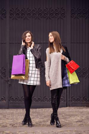two beautiful fashion models with shopping bags, posing outside, on dark background;  two young women laughing, having fun Reklamní fotografie