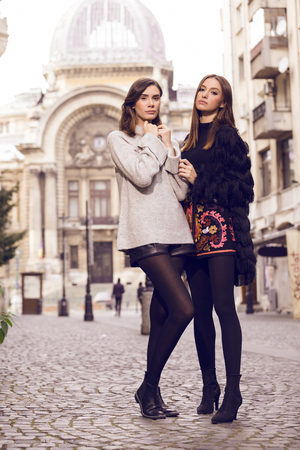 ankles sexy: two beautiful fashion models posing outside wearing a grey sweater with leather shorts, studded chelsea ankle boots and a fringed cardigan, black T-shirt, embroidered A-line skirt  heeled ankle boots
