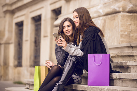 yellow jacket: two beautiful fashion models with shopping bags; two young women laughing, having fun, checking the phone, or taking a selfie; shopping break