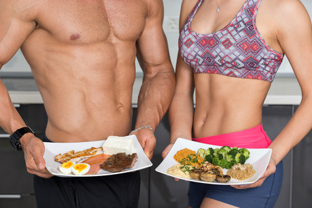 food woman: fit couple in the kitchen; animal versus plant proteins: one plate with beef, eggs, salmon, cheese and chicken grill and another with nuts, mushrooms, broccoli, lentil, hummus and quinoa Stock Photo