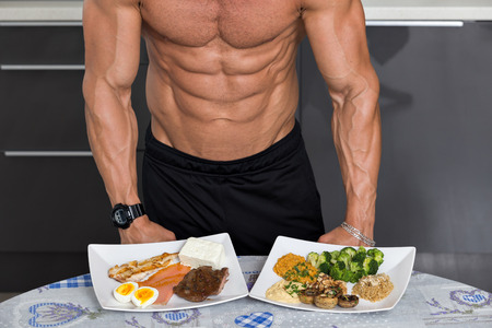 culturista: aptos hombre joven. culturista en la cocina; animales frente a las proteínas vegetales: plato con carne de res, huevos, salmón, queso y pollo a la parrilla y otro con frutos secos, champiñones, brócoli, lentejas, puré de garbanzos y quinoa Foto de archivo