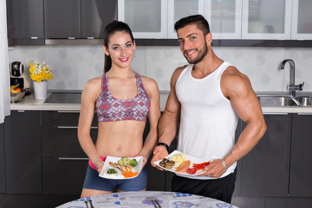 fit: fit couple in the kitchen, holding plates of healthy food: rice, chicken grill, broccoli, carrots, mushrooms, potatoes, salmon, tomato, red peppers Stock Photo