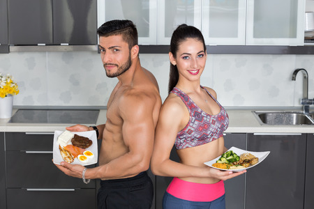 chicken and egg: fit couple in the kitchen; animal versus plant proteins: one plate with beef, eggs, salmon, cheese and chicken grill and another with nuts, mushrooms, broccoli, lentil, hummus and quinoa Stock Photo
