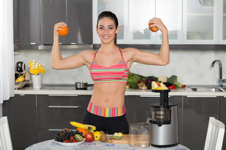 young fit woman in the kitchen, front double biceps with an orange and an apple